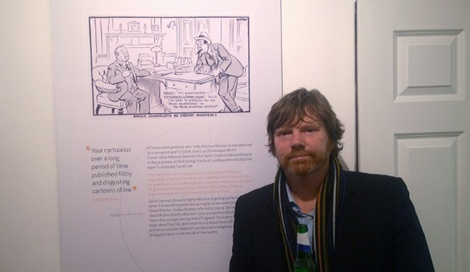 Mark with one of David Low's cartoons